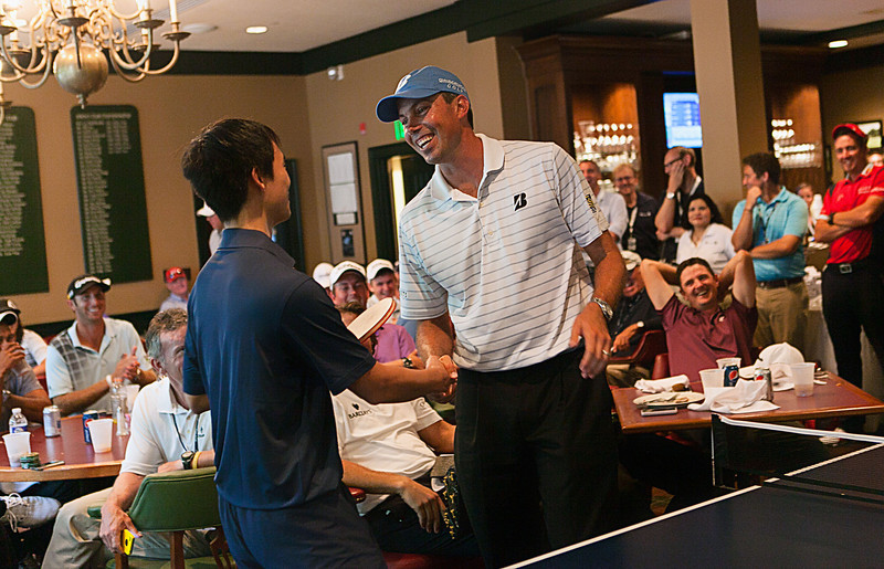 Matt Kuchar shakes hands with United States ping pong Olympian Timothy Wang after playing a match in the players clubhouse while waiting out a rain delay during the pro am at Crooked Stck golf course in Carmel Indiana on Wed. Sept. 5, 2012. (Charles Cherney/WGA)