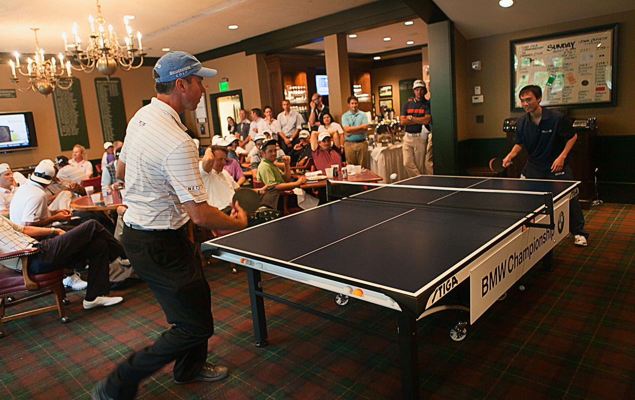 Matt Kuchar plays United States ping pong Olympian Timothy Wang in the players clubhouse while waiting out a rain delay during the pro am at Crooked Stck golf course in Carmel Indiana on Wed. Sept. 5, 2012. (Charles Cherney/WGA)