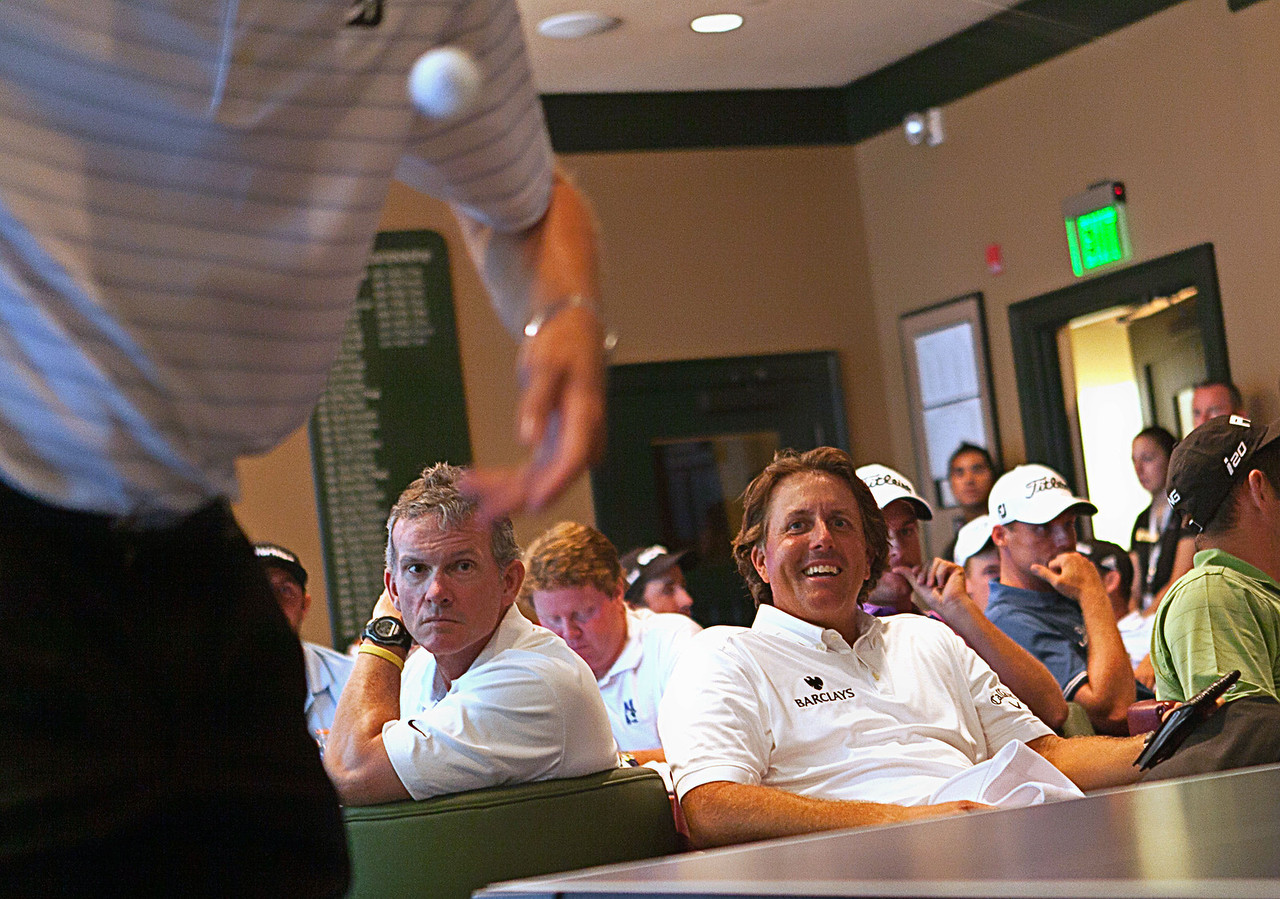 Phil Mickelson watches Matt Kuchar play United States ping pong Olympian Timothy Wang in a ping pong match in the players clubhouse while waiting out a rain delay during the pro am at Crooked Stck golf course in Carmel Indiana on Wed. Sept. 5, 2012. (Charles Cherney/WGA)