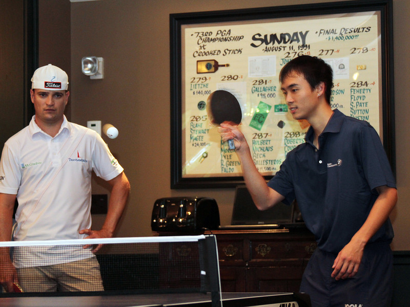 United States ping pong Olympian Timothy Wang shows Zach Johnson how it's done in the players clubhouse while waiting out a rain delay during the pro am at Crooked Stck golf course in Carmel Indiana on Wed. Sept. 5, 2012 (Ian Yelton/WGA).