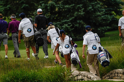 Evans Scholar caddies make a trek across one of the bridges during the BMW Championship Exhibition at Conway Farm Golf Club on Monday, Aug. 12. The nine-hole exhibition raised $45,000 for the Evans Scholars Foundation, the sole beneficiary of the BMW Championship.  The BMW Championship, the third of four events in the PGA TOUR's FedExCup Playoffs, will be held the week of Sept. 9-15 at Conway Farms. WGA Photo/Charles Cherney)