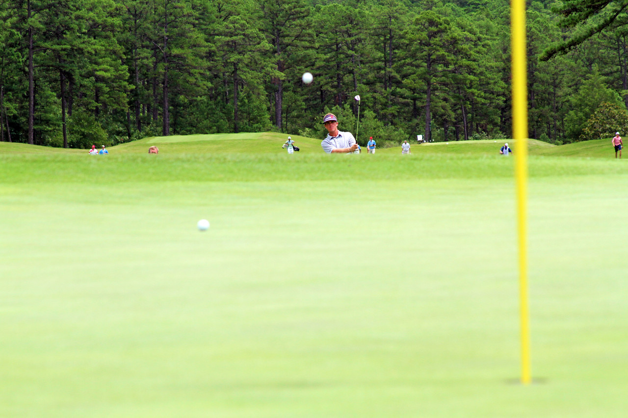 Sean Dale of Jacksonville, FL watches this wedge shot land on the putting surface during the match play portion of the 111th Western Amateur at The Alotian Club in Roland, AR. (WGA Photo/Ian Yelton)