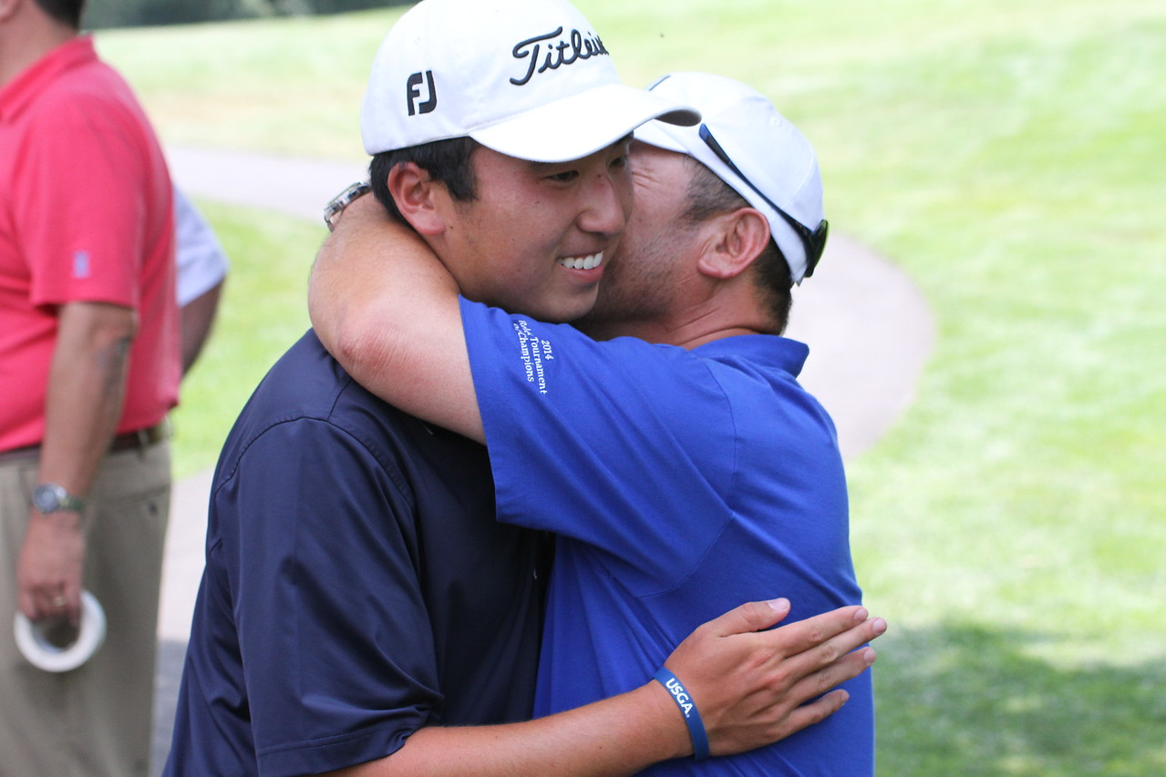 Doug Ghim and his father share a hug after Ghim's record-setting round, which also gave Ghim the tournament leading heading into the third round.