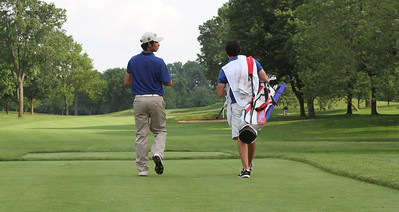 James Yoon,Bradenton, Fla., walks down the fairway with his caddie.