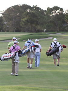 The first threesome of the day walks down the fairway after teeing off on hole No. 1.