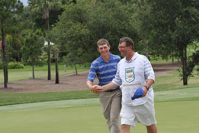Adam Wood and his father shake hands walking off the 18th green Friday after Adam made his final putt to seal his victory.