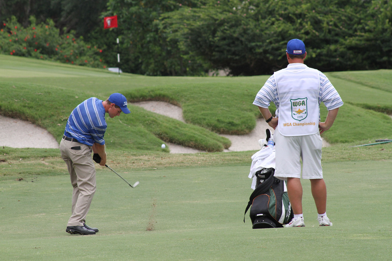 Adam Wood, the tournaments victor, launches a wedge toward the green as his father, who caddied for him, looks on.