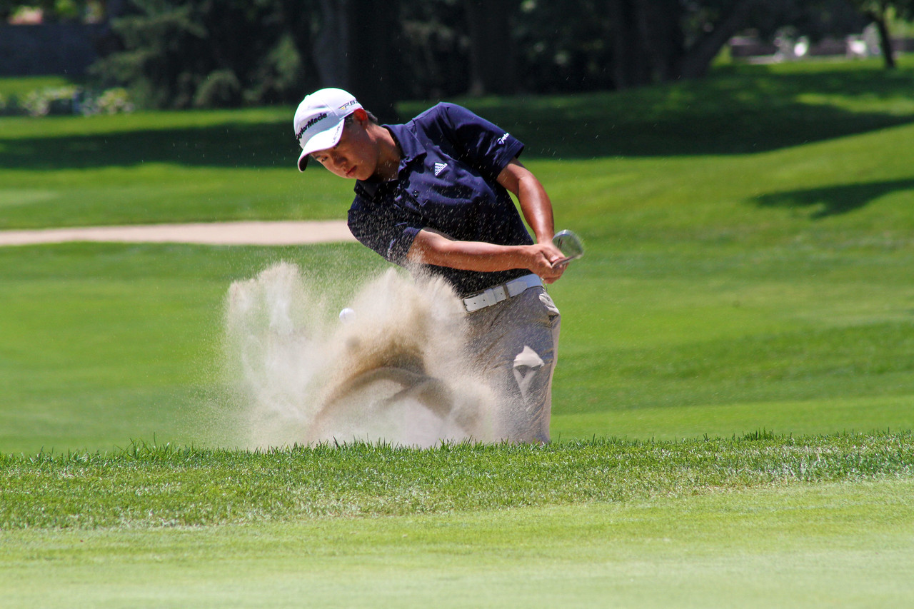 Collin Morikawa of La Canada Flintridge, Calif., blows his ball out of the sand during the final round of the 96th Western Junior at Meridian Hills Country Club.