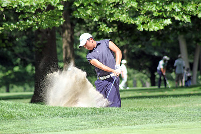 A junior blasts his ball out of the light colored sand to the right of the 12th green at Meridian Hills Country Club during the 96th Western Junior. (WGA Photo/Ian Yelton)