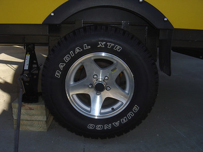 Jack up PUP.  Note the jack should be as close to the tire as possible and you will have to raise the PUP higher than is needed to remove a flat tire so that the spare can be placed on the hub.