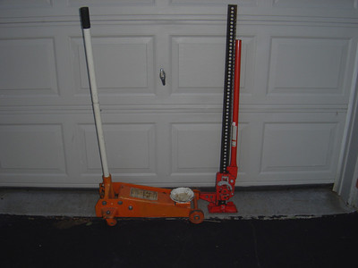 Large Floor jacks (left) are useful at home but too heavy to take on the road.  A high lift Jack (right) will not reach under the PUP to the frame.