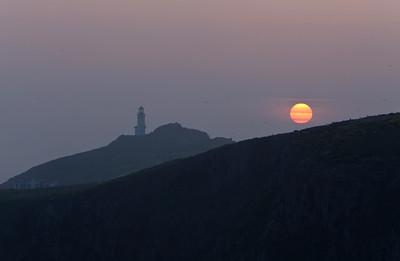 Sun rising next to lighthouse