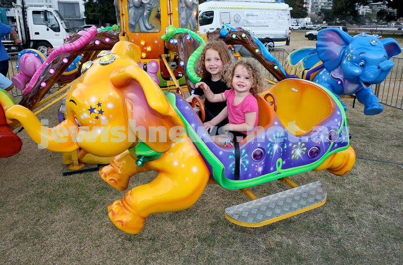 Double Bay Chanukah Party in Steyne Park. Temima & Bassi Apple have fun on a ride. Pic Noel Kessel.