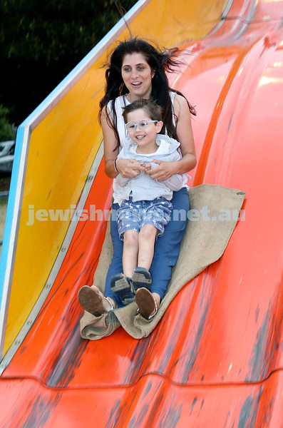 Chanukah at The Bay. Anita Birges slides down the giant slide with her son Joshua. Pic Noel Kessel.