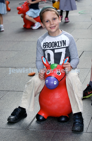 Chanukah in Martin Place. Pini Althouse on a bouncing animal. Pic Noel Kessel.