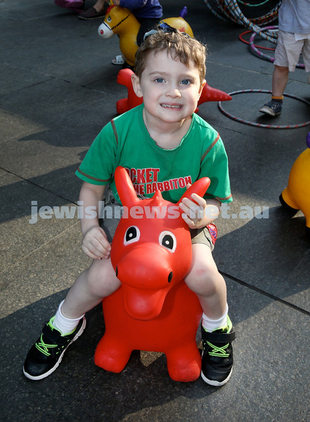 Chanukah in Martin Place. Joshua Guthrie has fun on a bouncing animal. Pic Noel Kessel.
