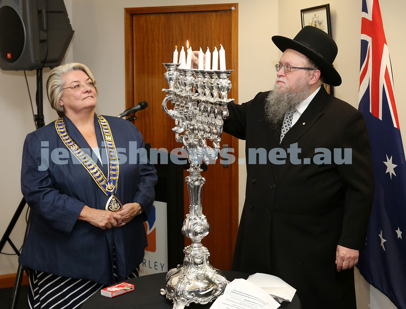 Waverley Council Chanukah Party. Rabbi Pinchus Feldman lights the Menorah with Waverley lord Mayor Sally Betts.