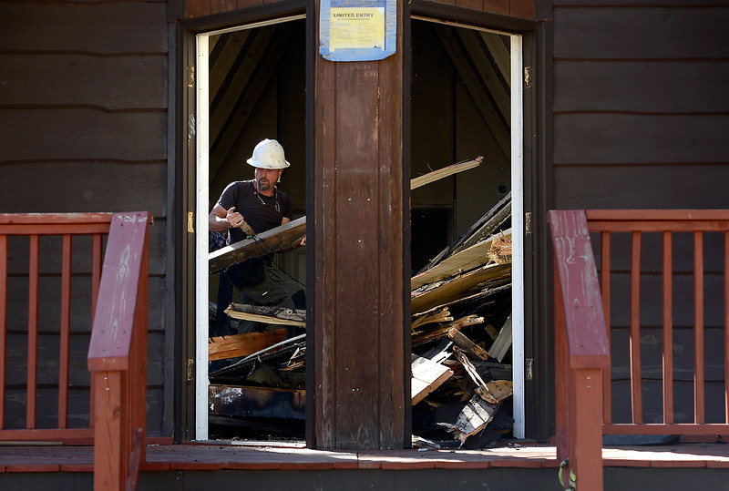 Scott Haney with Agritrack, Inc. takes a break from demolishing the Interlude Chapel to save timbers that church members want to use to build a cross Wednesday, July 13, 2016, in Drake. The chapel was damaged by the flood in 2013 and then repaired. In March it was damaged by a fire and now has to be demolished and rebuilt to code. (Photo by Jenny Sparks/Loveland Reporter-Herald)