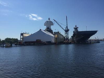 An amphibious assault ship (not an aircraft carrier, though it carries aircraft) and another ship covered up for sandblasting