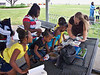 """Children gather to listen as VMN Peninsula Chapter Member Jackie Roquemore discusses the critters of the """"Luggage Zoo"""" at the 12th Annual Stand for Children Day Festival on June 6, 2009 at Buckroe Beach in Hampton."""