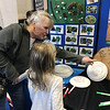 RMN Volunteer Pat Klima explains tree rings to a young participant.  Behind Pat is a tree match game for parents.  Can you match the seed or seed pod to the tree and then name the tree?