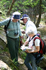 Ruth Douglas, Nancy Gercke, and Bob Henricks scramble the rocks in search of yellowroot. (Photo by Michelle Prysby)