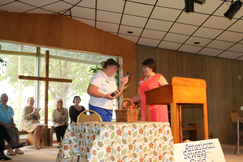 "Kathy accepts a well deserved award from Paulette for ""Member of the Year 2014"". Kathy spent countless back breaking hours transporting machines and supplies in and out of storage to camps, fair booths and meetings."