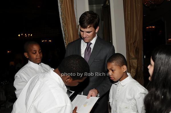 Eli Manning, members of the Little Flower Glee Club<br /> photo by Rob Rich © 2010 516-676-3939 robwayne1@aol.com