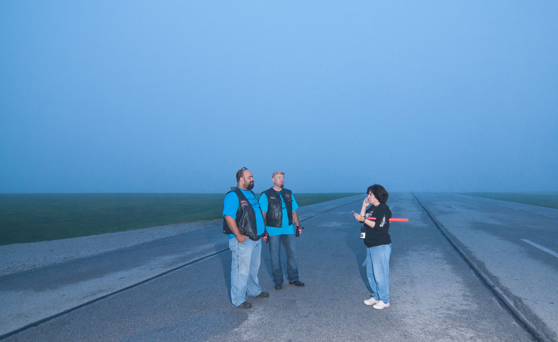 0717 - Talladega and California - BACA members Buddha and Bravo talking with Penny about the routing of traffic coming into the registration area. Not a morning for a pretty sunrise. This picture was taken 17 minutes after sunrise.