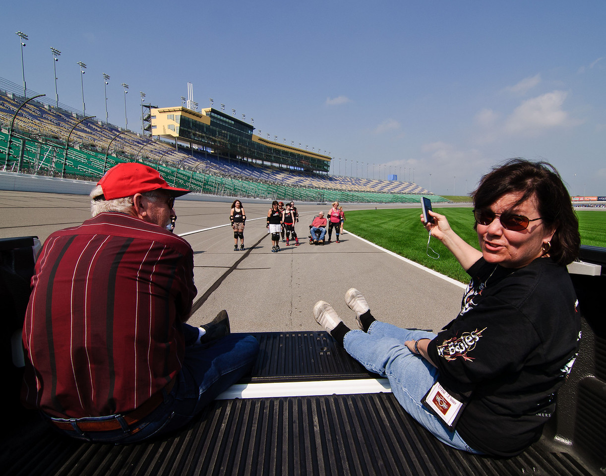 1407 - front stretch of track - a photographer and Penny ride in the back of a truck, taking pictures of Don and the roller girls as they make their way down the track.