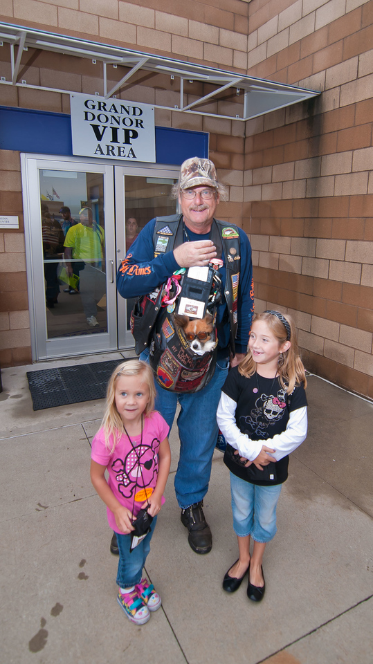 """0846 - just outside the Media Center doors - two girls pose to have their picture taken with a motorcycle goggle wearing dog. The pooch was taking part in Bikers for Babies with its owner, one of the """"Grand Donors"""". As you might expect, Grand Donors are participants who raise $1,000 or more for the Bikers for Babies event. I'm guessing that since both girls are wearing VIP tags that one or both were premature babies."""