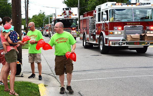 Debbie Blank | The Herald-Tribune<br /> Batesville firefighters pass out play fire helmets to kids along the parade route.