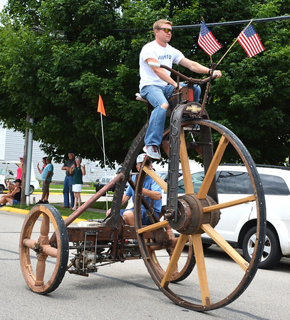 Debbie Blank | The Herald-Tribune<br /> A man steers an antique or reproduction high-wheel bicycle owned by Denis Schrank (seated in back).