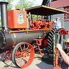 "The man with his hand on the gear switch of this Gaarscott-steam-engined tractor--on display at the Summerfest--also rebuilt it in 2010. He's a ""sixth-generation steam guy"" who's passing the knowledge along to the seventh-generation, cousiin Jack Struewing, 9. But that's not enough: Sam Hertel named his son Gaarscott, and says, ""there's a lot of story to be told behind the machine you see here."""