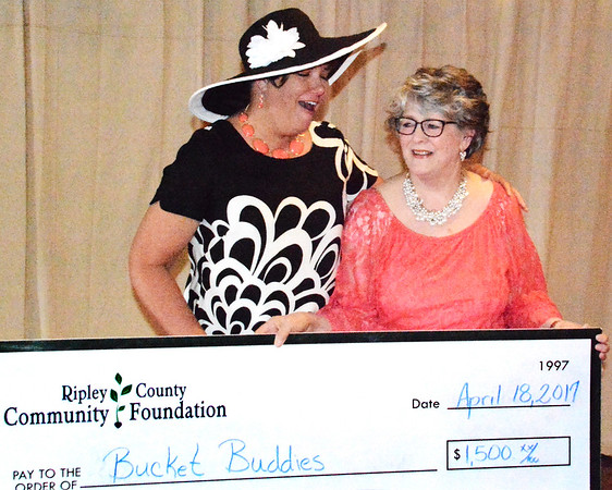 Debbie Blank | The Herald-Tribune<br /> Deanna Young (left), Napoleon, was surprised when her nonprofit, Bucket Buddies Mission, received a $1,500 grant.  Presenting the check is Lin Phaneuf. Attendees chose the organization from a handful of local projects.