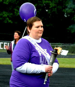 "Debbie Blank | The Herald-Tribune Brittany Lohrum, who was diagnosed with stage 4 Hodgkin's lymphoma, led the cancer survivors procession by carrying a torch. ""I went into remission in December,"" reported the Milan woman."