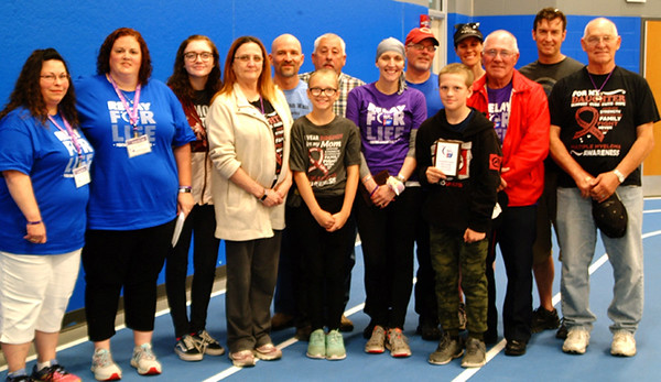 """Debbie Blank   The Herald-Tribune<br /> The Ripley County Relay for Life Compassion Award went to the family of Mandy Scott (in purple). On May 18, her daughter shaved Scott's head. To feel that she wasn't fighting cancer alone, the patient then shaved the heads of her husband, father, four uncles, two sons and other male relatives. """"In that moment, you could feel the love all those guys had for Mandy,"""" recalled cousin Cindy Lamping (far left) with co-lead Samantha Smith."""