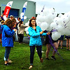 Debbie Blank | The Herald-Tribune<br /> A volunteer passes out white balloons to caregivers of cancer patients, who took the second lap of the Ripley County Relay for Life at the Batesville High School track.
