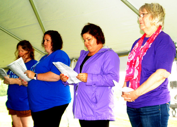 "Debbie Blank | The Herald-Tribune<br /> Barbara Eades (right), St. Paul Lutheran Church, Olean, team leader, presented the opening prayer before laps began. Also participating in the ceremony were (from left) relay co-leads Carrie Oppelt and Samantha Smith and committee member Kari Ann Rennekamp, who told survivors, ""All of you are an inspiration."""