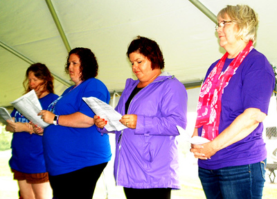 "Debbie Blank | The Herald-Tribune Barbara Eades (right), St. Paul Lutheran Church, Olean, team leader, presented the opening prayer before laps began. Also participating in the ceremony were (from left) relay co-leads Carrie Oppelt and Samantha Smith and committee member Kari Ann Rennekamp, who told survivors, ""All of you are an inspiration."""