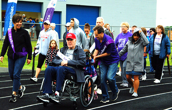 Debbie Blank | The Herald-Tribune<br /> Survivor Jim Dreyer (red cap), Batesville, is surrounded by children Teri Coleman and Dave Dreyer during the caregivers lap.