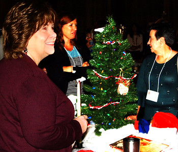 Debbie Blank | The Herald-Tribune Kim Inscho (from left), Theresa Fullenkamp and Dr. Kimberly Kick admire table decorations at We Help. We Heal. We Hope, Safe Passage's benefit Dec. 1 at The Barn at Walhill Farm.