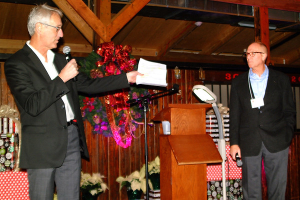 Debbie Blank | The Herald-Tribune<br /> Master of ceremonies Dan Mattingly (left) and live auctioneer Jeff Gratz kick off the event. Later Gratz auctioned off six items that brought in $11,000 for Safe Passage.