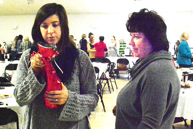 Debbie Blank   The Herald-Tribune As guests mingle and bid on silent auction items in the background, Olivia Montini (left), Connersville, and mom Chrissy Montini, Batesville, check out which kind of wine she won in the wine pull. Olivia donated $10, then chose a wrapped bottle.