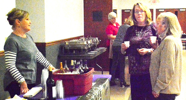Debbie Blank   The Herald-Tribune Patti Hoff (from left) of Ertel Cellars Winery offers tastings of many varieties to Mary Olsen, Bright, and Jenny Fritsch, Sunman.