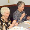 Debbie Blank | The Herald-Tribune<br /> After deciding which colors they would like, Batesville residents Jane Roberson (left) and Joan Stephens paint souvenir wineglasses.