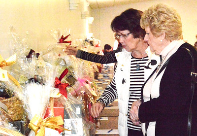 Debbie Blank   The Herald-Tribune Linda Gastright (left), Cold Spring, Kentucky, and Mary Kay Glaser, Fort Thomas, Kentucky, prepare to bid on a few of the many silent auction items, whcih ranged from designer purses to local gift certificates and services.