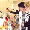 Debbie Blank | The Herald-Tribune<br /> Linda Gastright (left), Cold Spring, Kentucky, and Mary Kay Glaser, Fort Thomas, Kentucky, prepare to bid on a few of the many silent auction items, whcih ranged from designer purses to local gift certificates and services.