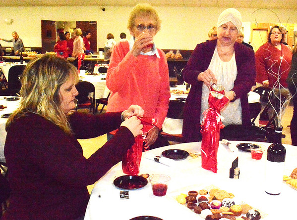 Debbie Blank | The Herald-Tribune<br /> Anna Mae Raver (center), Oldenburg, and daughters Monica Livers (left), Oldenburg, and Diane Raver, Batesville, participated in the wine pull. After each donated $10, they unwrapped bottles to see the varieties. The festive atmosphere at the Batesville Knights of Columbus Hall included cheese and crackers, grapes and sweets at each table for the 280 attendees.