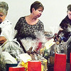 Debbie Blank | The Herald-Tribune<br /> Joan Lohrey (from left) and Micki Strohmier, Brookville, and Edith Lecher, Enochsburg, check out Chinese raffle baskets.